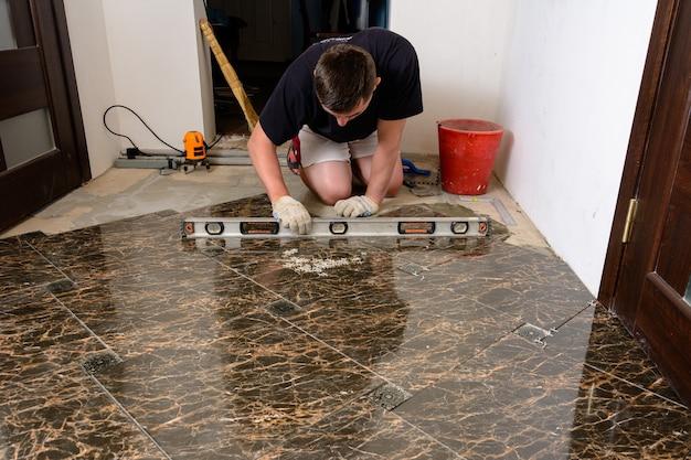 Мастер проверяет уровень плитки поверхности плитки.