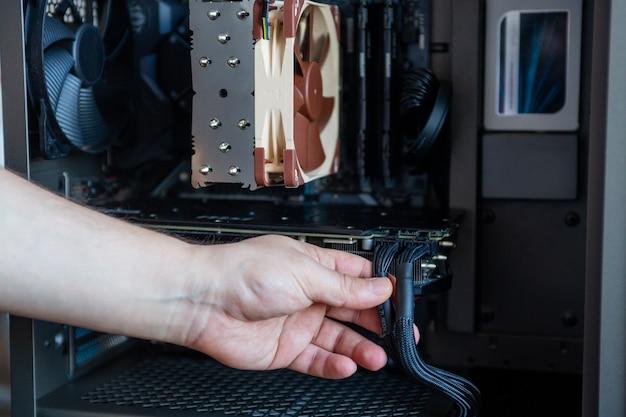 Мастер собирает / ремонтирует компьютер, системный блок компьютера изнутри крупным планом