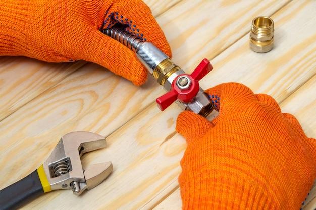 Мастер соединяет кран и шланг гаечным ключом для газопровода.