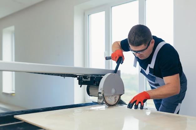 Мастер режет плитку. мужчина обращается с камнем и большой керамической плиткой