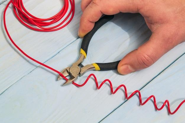 마스터 전기 기사가 대각선 절단 펜치로 빨간색 와이어를 절단합니다.