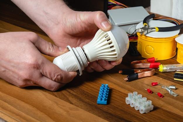 마스터 전기 기술자가 전구를 켭니다.
