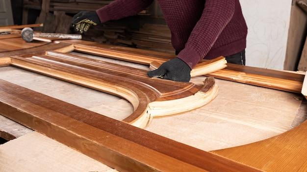 マスターはワークショップで木製のドアの修復に従事しています