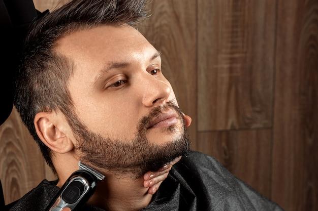 マスターは、電気機械、トリマー、クローズアップでクライアントにひげの散髪をします。美容院でひげを剃るプロセス。ボディケア、ライフスタイル、メトロセクシャル。