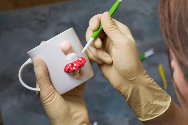 Мастер делает фигурку человека на кружке из полимерной глины.