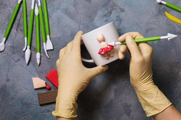 Мастер лепит фигурку человека на кружке из полимерной глины.