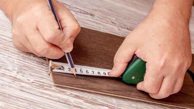マスターは巻尺で木材に印を付けます