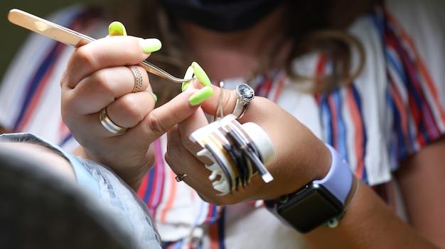 まつげエクステのマスターはモデルの前に座って、ピンセットでまつげの束を保持して接着剤に浸します