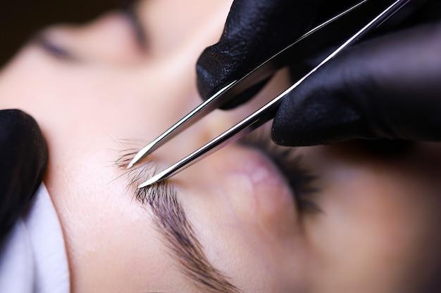 Мастер перманентного макияжа подготавливает брови клиентки к процедуре, выщипывая волоски пинцетом.