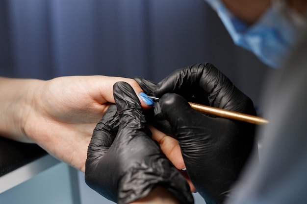Мастер красит ногти синим лаком. маникюр в салоне красоты