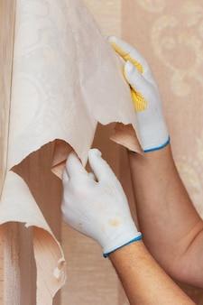 マスターは壁から古い壁紙を取り除きます。アパートの修理