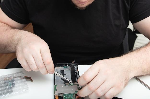 주인은 휴대 전화를 수리하고 특수 도구로 예비 부품을 설치합니다.