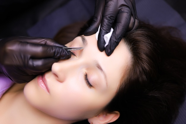Мастер-татуировщик подготавливает брови к выщипыванию лишних волосков, подготавливает контур бровей к нанесению татуировки.