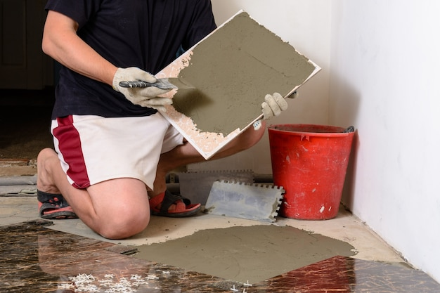 Мастер плитки размазывает клейкий раствор на мраморную плитку.