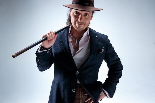 Зрелый бородатый человек в костюме и шляпе, холдинг трость. изолированный на серой студии.