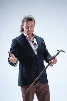 Зрелый бородатый мужчина в костюме держит трость.