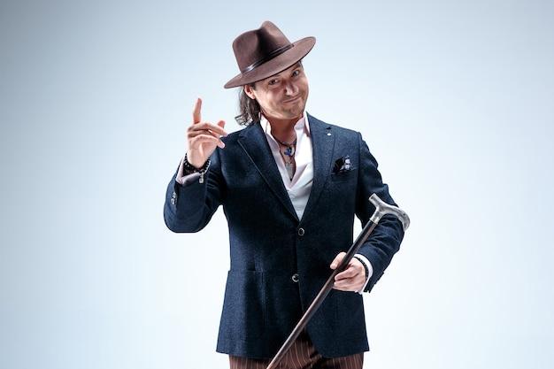 杖を持ったスーツと帽子の成熟した男。灰色のスタジオの背景に分離されました。