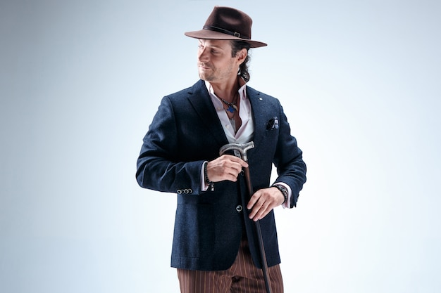 Зрелый человек в костюме и шляпе, холдинг трость. изолированный на серой студии.