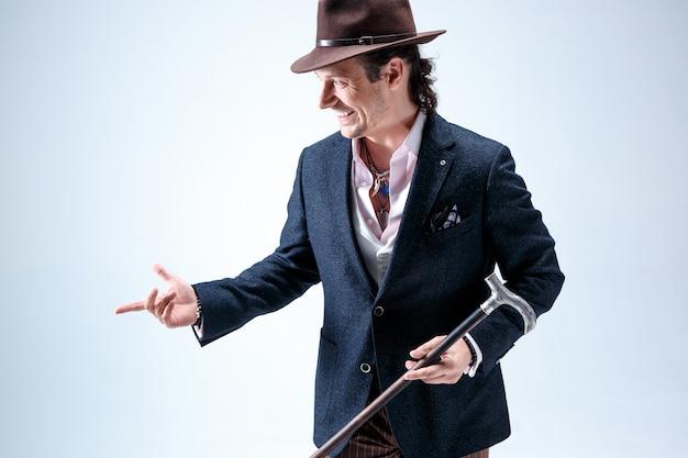 スーツと帽子を持った杖を持った中年の男性。