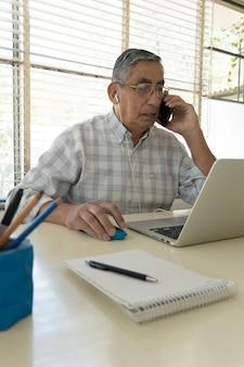 Зрелый мужчина сидит дома за столом и пользуется мобильным телефоном и ноутбуком.