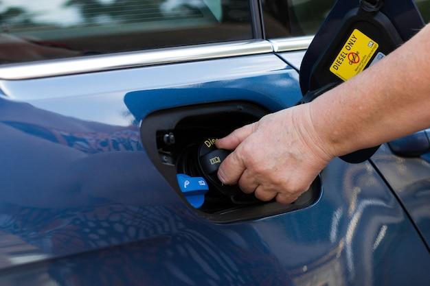 성숙한 여성은 연료를 보급한 후 자동차의 연료 캡을 닫습니다.
