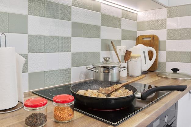 肉はキッチンのインテリア、調理器具の背景に鍋で揚げられています