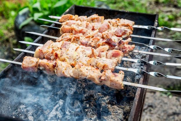 Мясо на гриле в барбекю на природе. крупный план. активный отдых и здоровое питание.