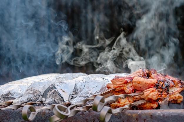 Мясо на металлических шпажках заворачивают в алюминиевую фольгу и жарят на углях.