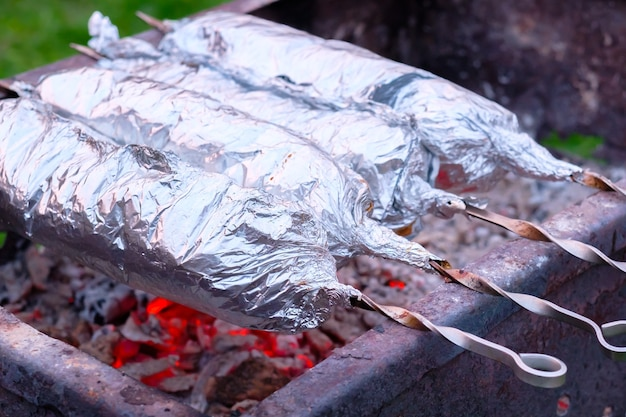 金属串の肉をアルミホイルで包み、炭火で焼く