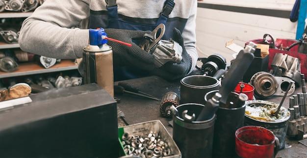 作業中の自動車部品の1つを修理する整備士