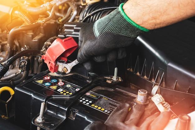 メカニックの手は、車の古いバッテリーの交換にオープンエンドレンチでボルトを固定します