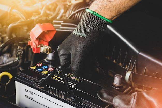 メカニックの手が交換のために車の古いバッテリーを引き上げています