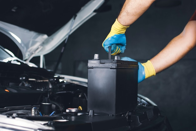 정비사 손이 교체를 위해 자동차의 오래된 배터리를 뽑고 있습니다
