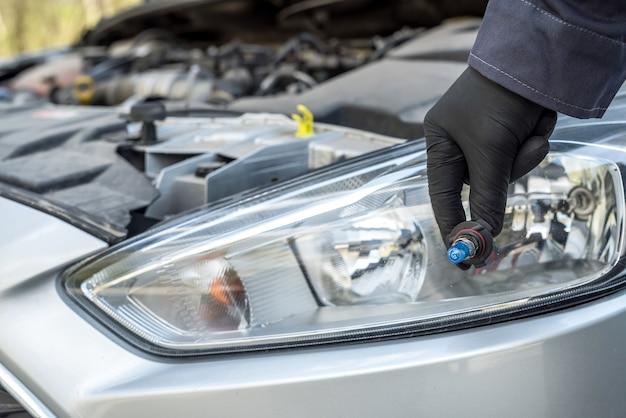 정비사는 자동차 헤드 라이트의 할로겐 전구를 교체합니다. 자동 기술