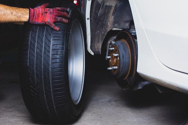Рука механика держит колесо из легкого сплава для замены колеса из легкого сплава в ступицу колеса в магазине автомобильных шин.