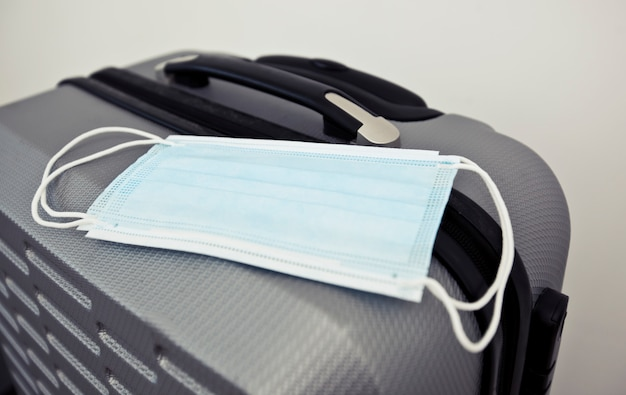 Медицинская маска на чемодане как необходимая вещь в путешествии в постсоветское время