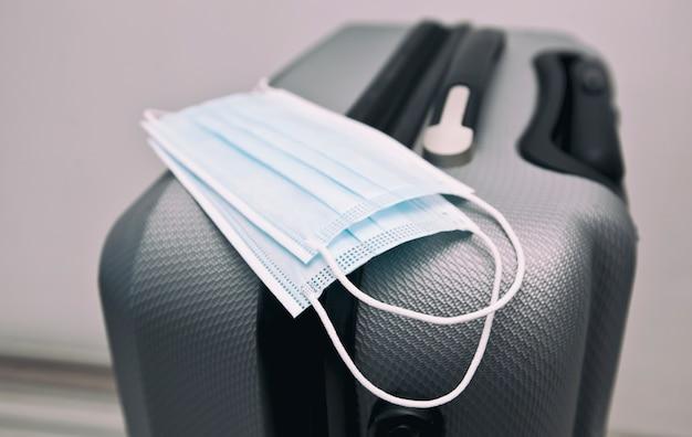 Медицинская маска на чемодане как необходимая вещь в путешествии в пост covid-19 время