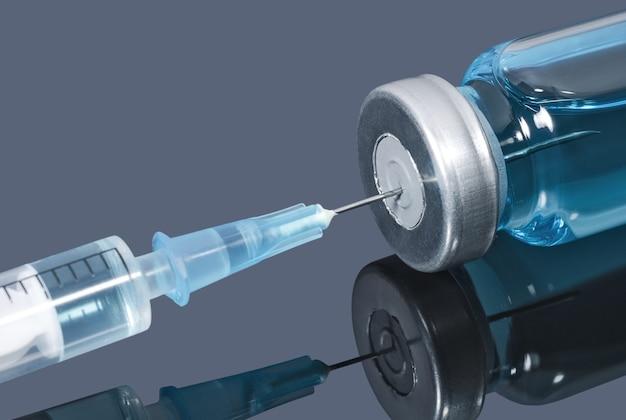 医療用針は、暗い背景に青い液体でバイアルに槍で刺されました
