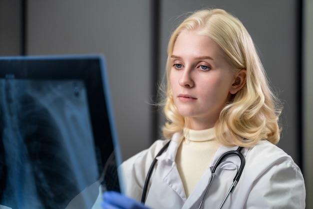 의료 종사자가 rentgens 사진을 조심스럽게 바라본다.