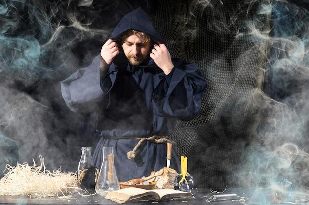 中世の錬金術師がテーブルで魔法の儀式を行う