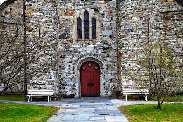 赤い入り口のある中世の石造りの教会