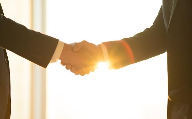 日当たりの良い背景で男性の握手
