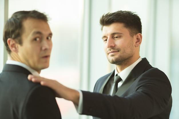 남자들은 사무실에서 어깨를 잡고 있다
