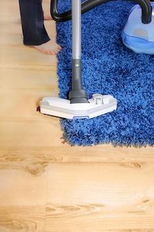 작동 중인 진공 청소기의 금속 파이프 - 카페트와 합판 바닥을 청소합니다.