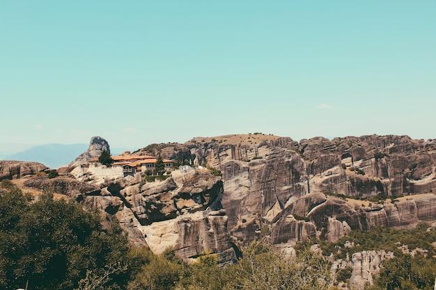 Монастыри метеоры, к востоку от гор пиндос в греции. каменистый горный пейзаж, голубое небо, зеленые деревья.