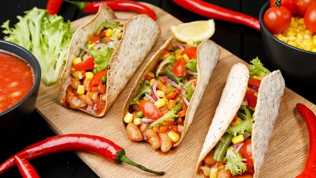 Мексиканское блюдо кукурузной лепешки тако с овощной начинкой на деревянной доске на черном фоне