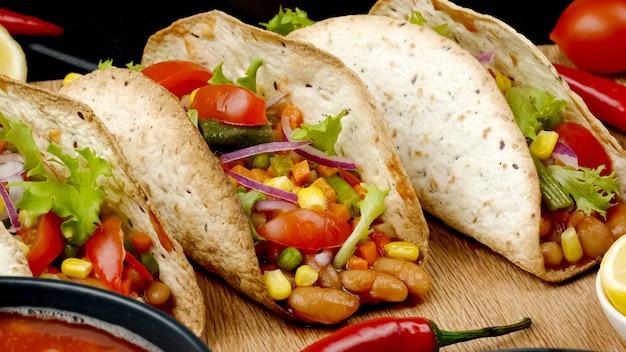 黒の背景に木の板に野菜を詰めたタコスコーンフラットケーキのメキシコ料理