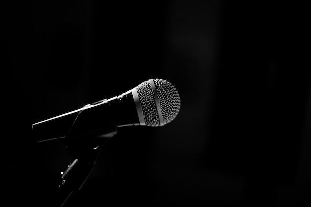 Микрофон для сцены стоит на подставке на черном фоне. черно-белая фотография.