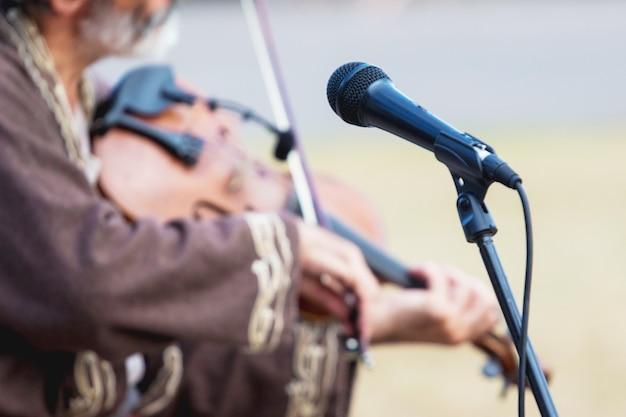 초점이 맞춰진 마이크와 흐릿한 바이올린을 든 음악가_
