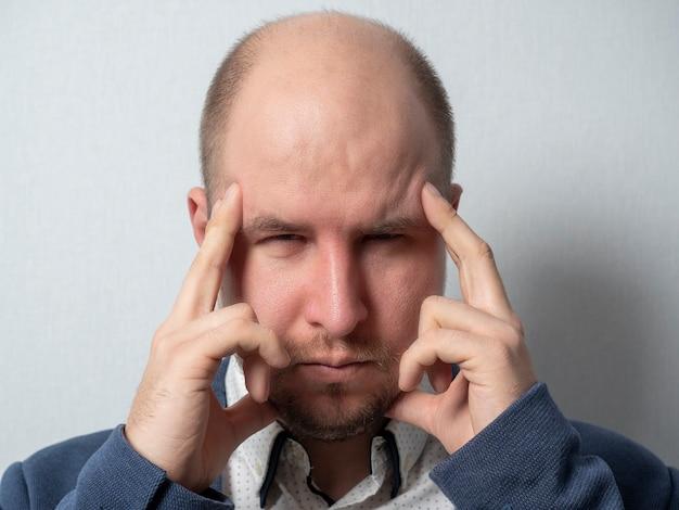 Мужчина средних лет в костюме приложил пальцы к голове и прищурился. сосредоточен, пытаясь вспомнить.